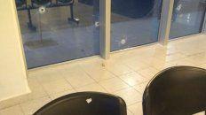 Vidrio y sillas perforadas por las balas.
