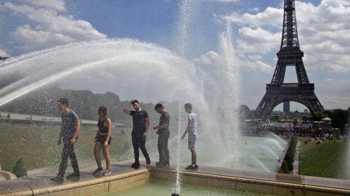 Al rojo vivo. Jóvenes franceses buscan algo de alivio en las fuentes de París junto a la torre Eiffel.