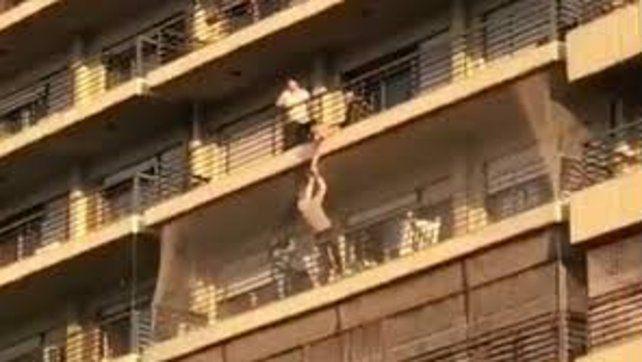 Tremendo. Un vecino sostiene desde abajo al nene que cuelga del balcón.
