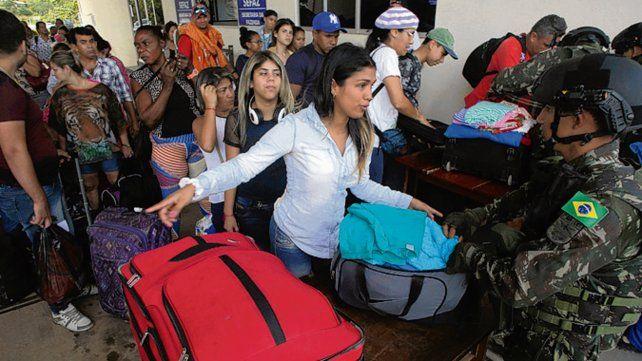 Controles. Un soldado brasileño inspecciona las valijas de una venezolana.