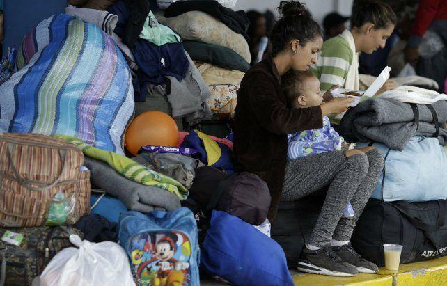 Una venezolana alimenta a su pequeño mientras aguarda un transporte para continuar viaje en Perú.
