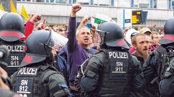 Tensión. Ultras saludan con el brazo en alto durante una protesta contra los inmigrantes en Chemnitz.