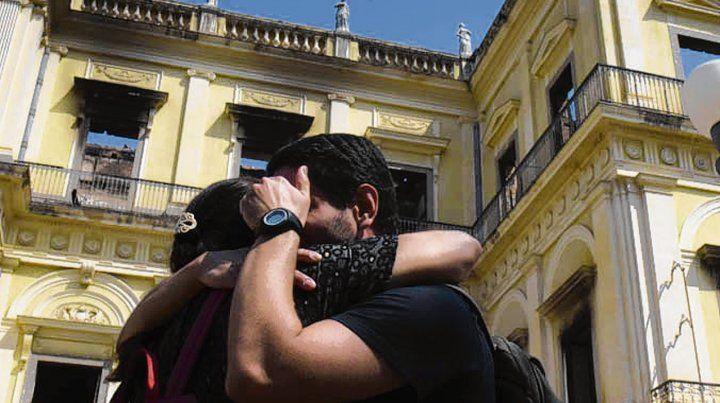 Desolador. Dos jóvenes se abrazan frente al Museo Nacional de Río.