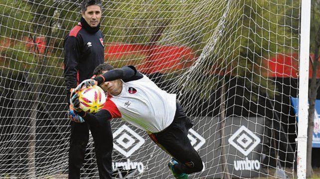 En la práctica. Aguerre vuela y detiene la pelota mientras Ibáñez espera su turno.