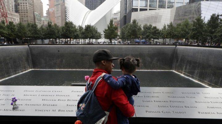 Tributo. Un hombre con su hija observa el memorial en donde se erigía la torre norte del World Trade Center.