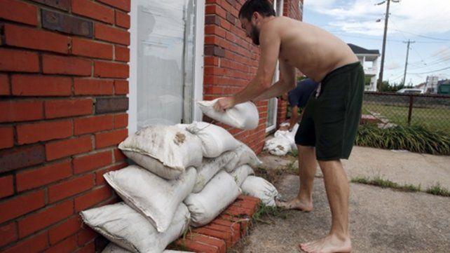 Temor. Un habitante de Norfolk sella las puertas con bolsas de arena.