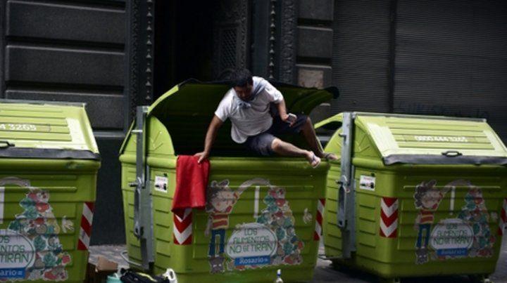 Postal de la crisis. En el centro de Rosario se repiten las escenas de gente hurgando en los contenedores de residuos.