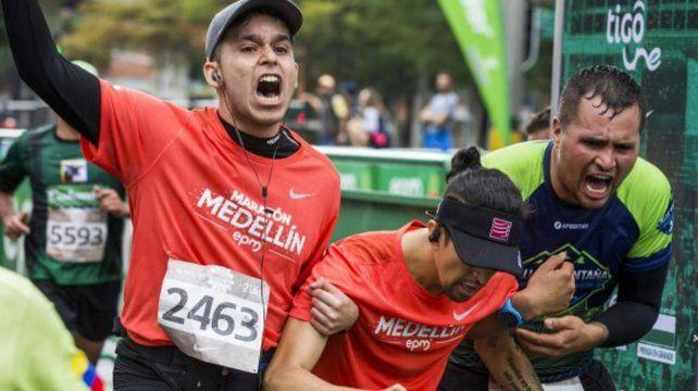 Arboleda es asistido por otros corredores al atravesar la meta.