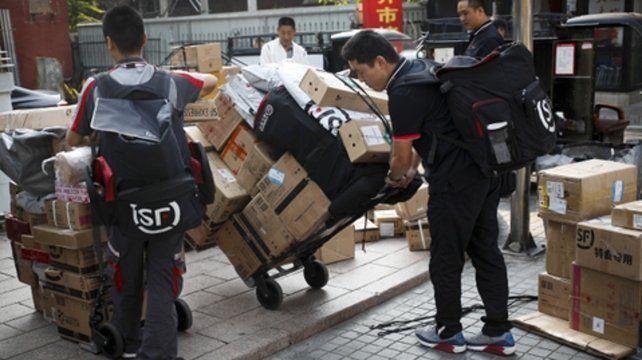 En peligro. Trabajadores trasladan mercaderías por las calles de Pekín. La guerra comercial no amaina.