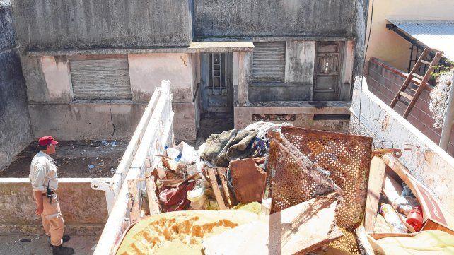 Nauseabundo. Obreros ayudan a la salida de camiones con residuos.