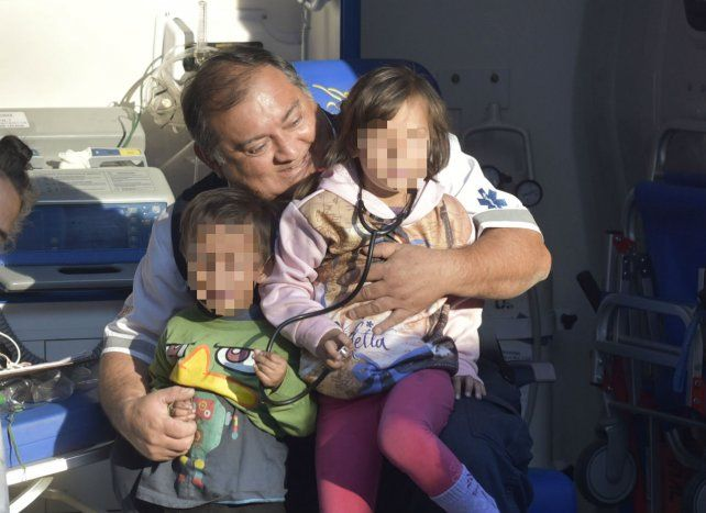A salvo. Los dos hermanitos junto a un paramédico, ayer, minutos después de haber sido rescatados.