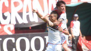 Sonrisa ancha. Víctor Figueroa celebra el gol de penal, con Formica sobre sus espaldas.