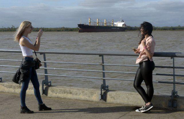 Foto en la costa. Dos jóvenes disfrutan el paisaje que se observa desde el área central de la ciudad.