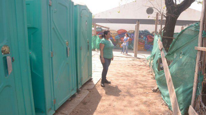 Afuera. La escuela se quedó sin baños y por eso la provincia instaló unos sanitarios químicos. En el patio se observan los tejidos de la obra inconclusa.