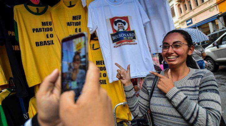Bolsonaritis. Una chica en San Pablo hace el gesto del candidato derechista junto a sus remeras.