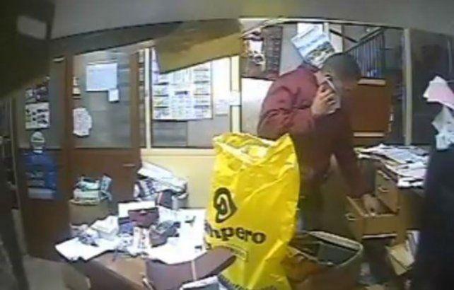 El policía de la Ciudad de Buenos Aires toma el dinero dispuesto en un cajón.