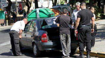 Agentes de control municipal inspeccionan a un auto denunciado por operar como remis trucho.