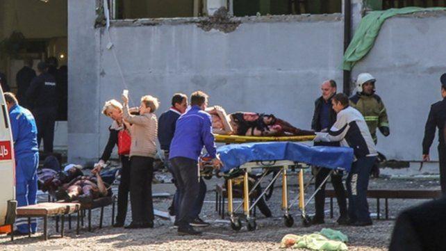 Atroz. Equipos médicos auxilian a las víctimas en la escuela de Kerch.