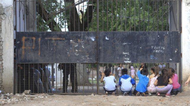 Niñas y niños del barrio Trujui espían por el portón del predio donde hallaron el cadáver de Sheila.