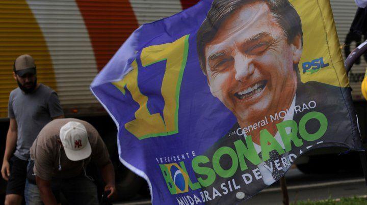 Ambiente caldeado. Un vendedor callejero exhibe banderas de Bolsonaro en la periferia de Brasilia.