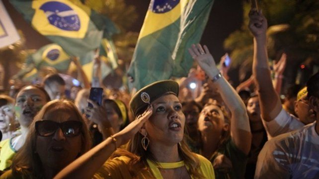 Firme. Una seguidora de Bolsonaro hace la venia ante su vivienda.