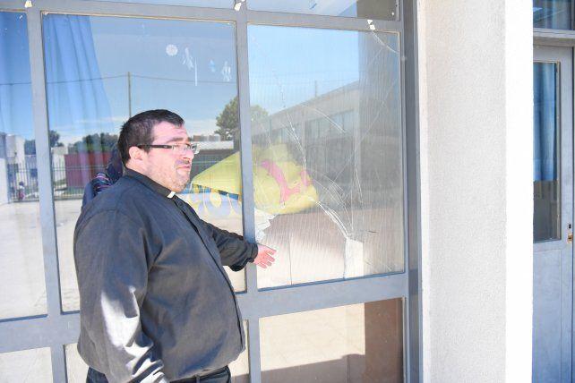 El padre Lucas muestra el lugar por donde entraron los ladrones a la escuela.