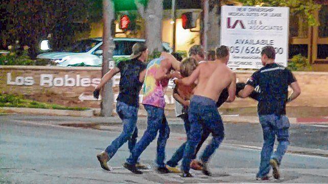 Masacre. Jóvenes trasladan a uno de los heridos tras el ataque ocurrido a unos 60 kilómetros de Los Angeles.