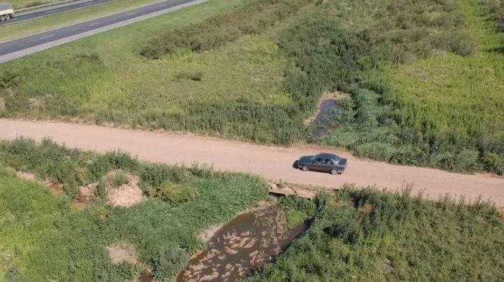 Foco contaminante. La imagen registra el volcamiento de líquidos en un canal paralelo a la autopista.