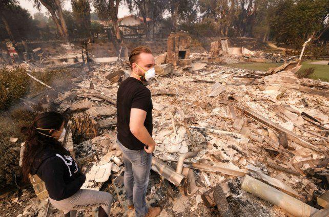 Devastación. Una joven pareja observa desolada los restos irreconocibles de su casa en Malibú.