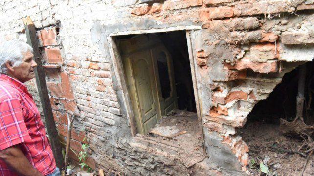 Un familiar de las víctimas observan cómo quedó la humilde casa tras el derrumbe.