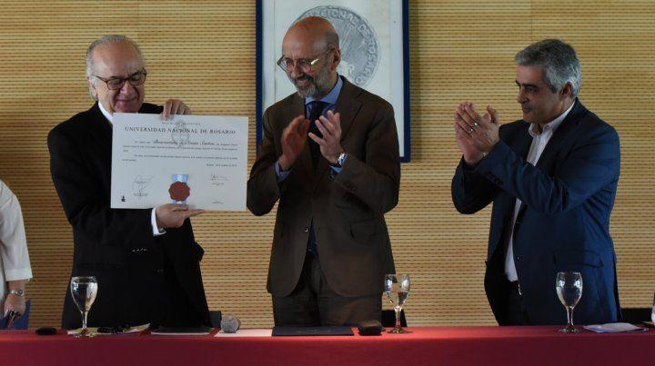 El diploma. El referente muestra el reconocimiento junto al rector de la UNR y el decano de Ciencia Política.