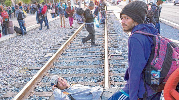 Freno judicial. Un grupo de migrantes descansan en un paso ferroviario en las inmediaciones de Tijuana.