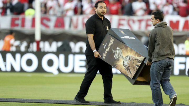 Empleados de la organización retiran el atril donde estaba la Copa Libertadores que buscan conquistar River y Boca.
