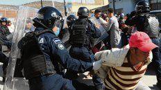 Migrantes forcejean con policías mexicanos en la frontera.