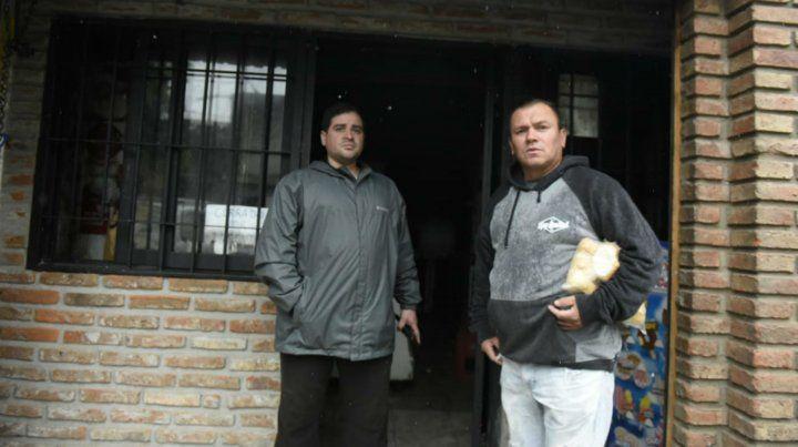 Dante Benítez (a la izquierda) junto a un vecino en la puerta del negocio que se incendió anoche.