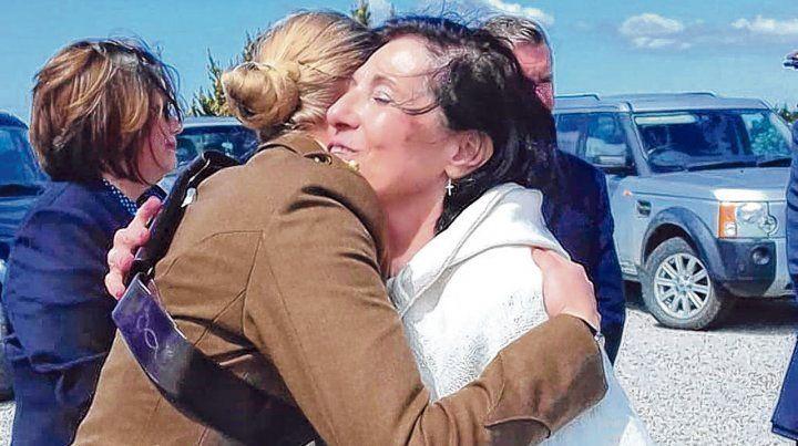 María Cristina Scavarda es saludada en Malvinas por una oficial británica tras recibir la bandera nacional.