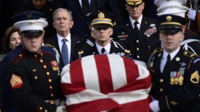 Despedida. Una guardia de honor traslada el féretro. Atrás Bush hijo.