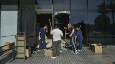 Esta mañana retiraban los cristales del ventanal que recibió los impactos de las balas.