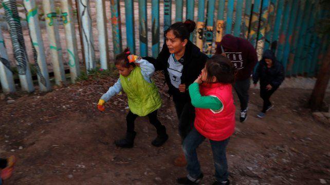 Tolerancia cero. Una centroamericana y sus hijos camina junto a la valla fronteriza tras intentar en vano cruzarla.