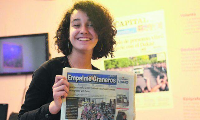 Sofía muestra orgullosa un ejemplar del diario barrial donde escribe.