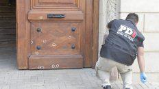las huellas del ataque. Un policía del gabinete criminalístico identifica los orificios que los balazos dejaron en la puerta del Concejo.