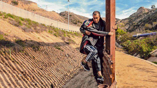 Meta riesgosa. Un centroamericano ayuda a su hijo a cruzar la valla que limita la frontera entre México y EEUU.