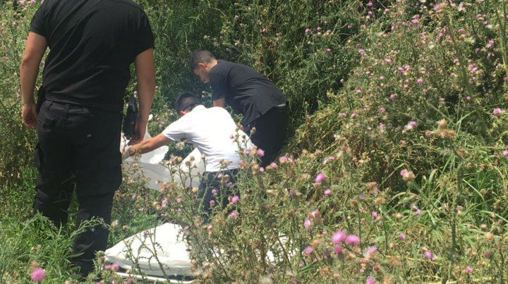 Peritos de la policía trabajan sobre el cadáver hallado en un zanjón cerca de la autopista.