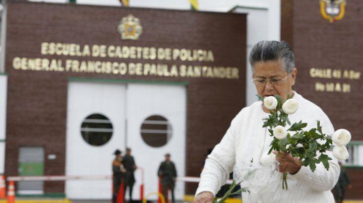 Muestras de dolor. Una mujer deposita flores frente a la academia policial en honor a los jóvenes fallecidos.