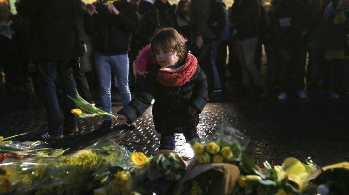 Una niña deja un ramo de tulipanes en la plaza Royale.