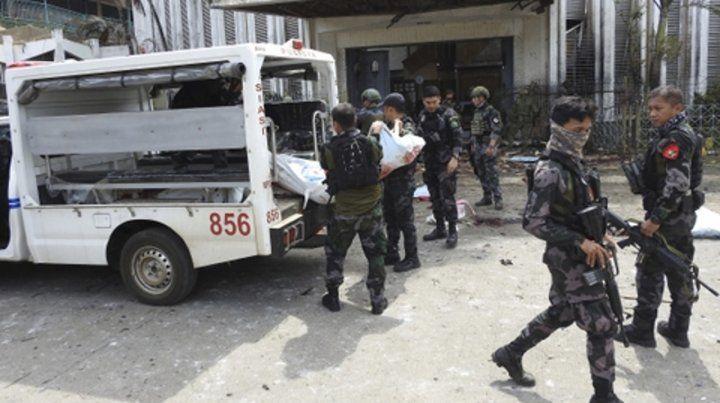 Víctimas. Los militares retiran cuerpos del interior de la iglesia atacada.