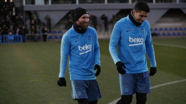 Felices los amigos. Messi y el uruguayo Luis Suárez se retiran de la práctica previa al superclásico por la Copa del Rey.