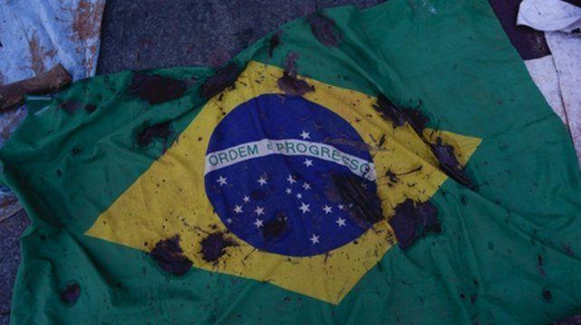 Tragedia. Una bandera cubierta de barro