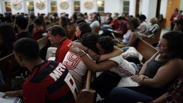 Duelo. Abrazos y llanto durante una misa en memoria de los chicos fallecidos entre las llamas.
