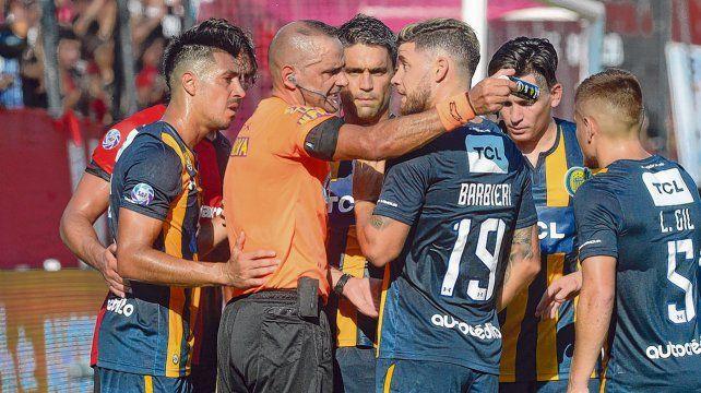 Reclamo. Los jugadores canallas discuten con Abal tras la patada de Callegari a Riaño.